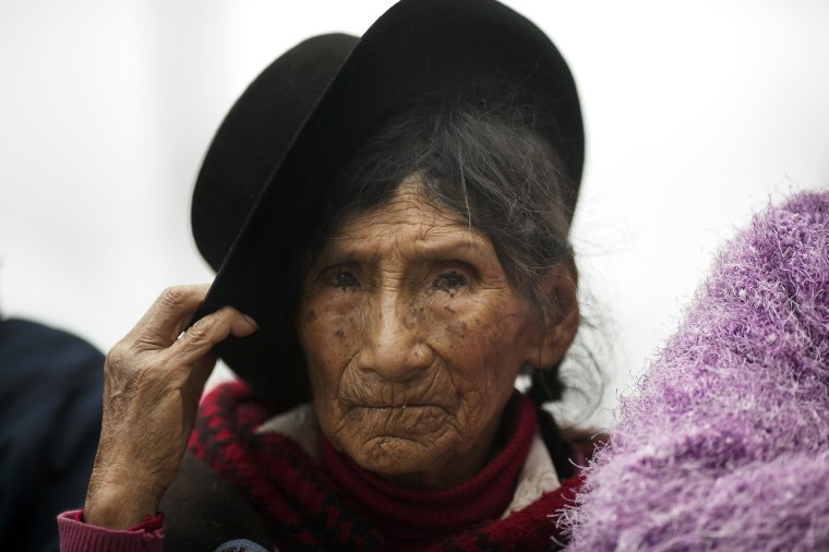 Image: A woman waits for the return of the remains of over 30 people who were killed more than two decades ago