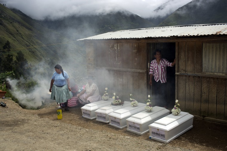 Image: Villagers gather next to coffins holding the remains of their loved ones