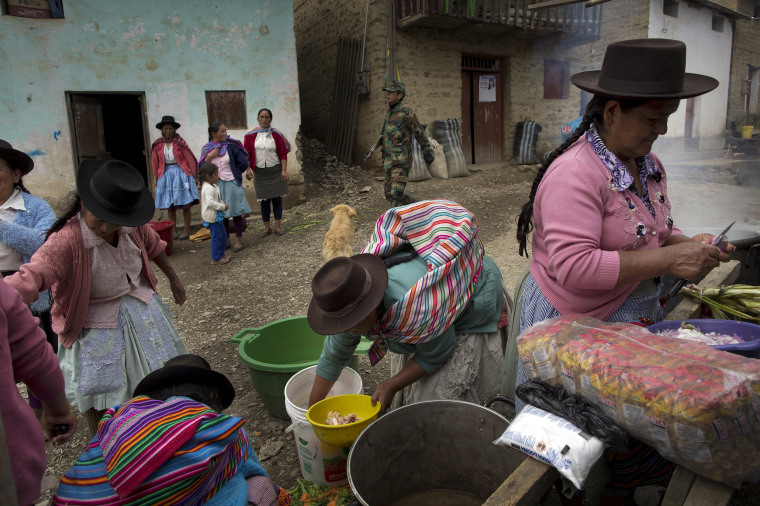 Image: Women prepare lunch during a group burial for people who were slain more than two decades ago by Shining Path guerrillas