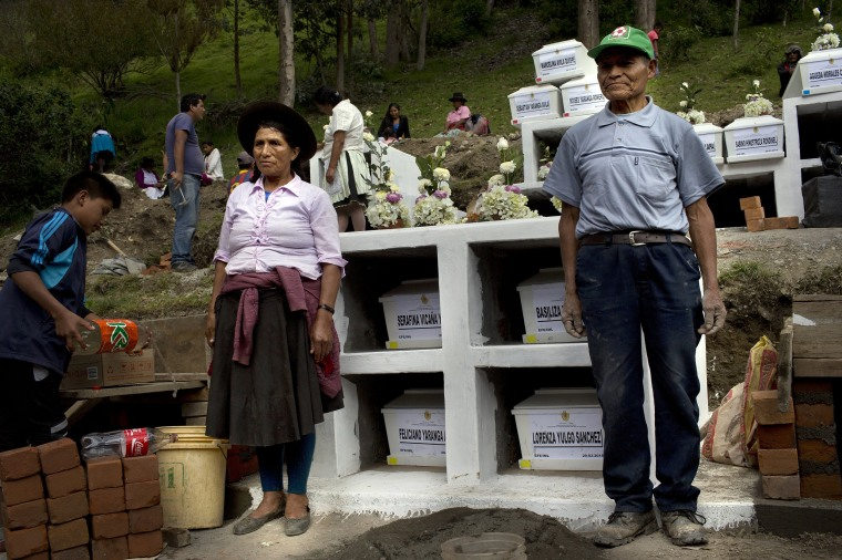 Image: Relatives pose for pictures next to coffins holding the remains of family members