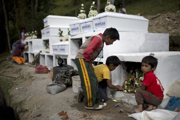 Image: Children light candles in one of the niches of over 30 people killed by Shining Path rebel