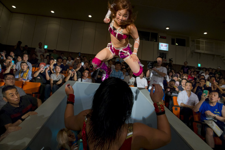 Image: Wrestler Kairi Hojo jumps at her opponent Mieko Satomura as they fight in the stands during a Stardom female professional wrestling show