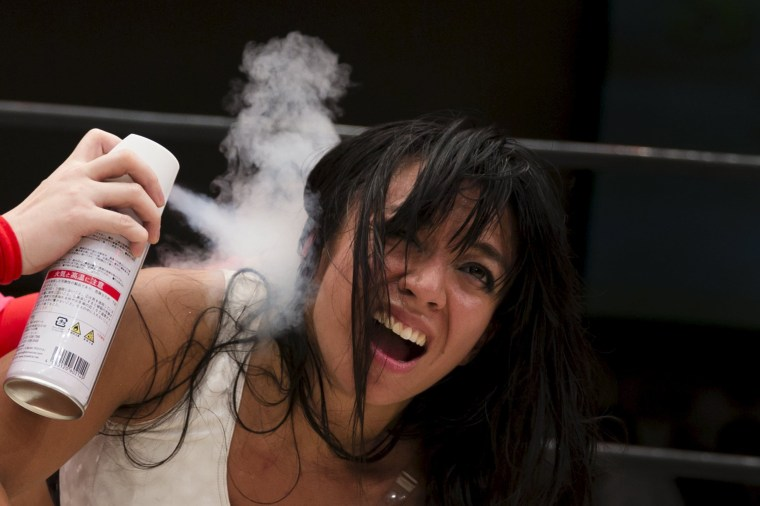 Image: Wrestler Kris Wolf receives ice spray treatment during her show