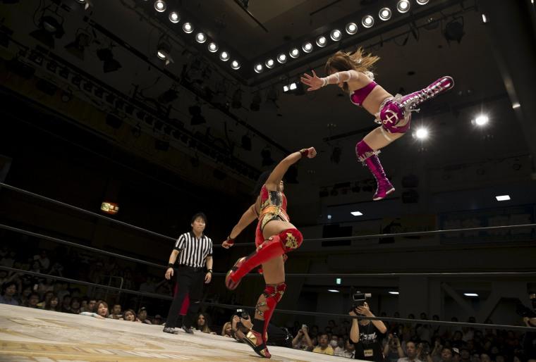 Image: Wrestler Kaori Housako jumps at her opponent Mieko Satomura