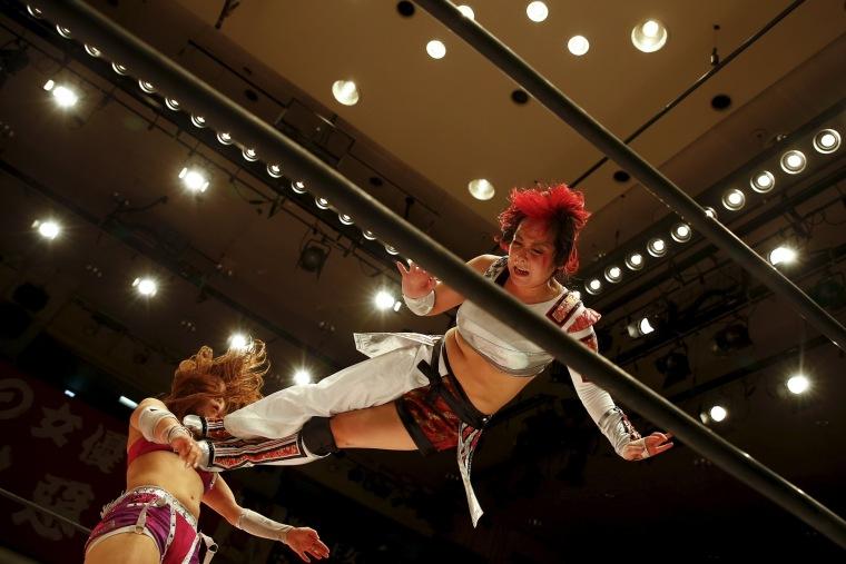 Image: Wrestler Act Yasukawa (R), jumps at Kairi Hojo during their show