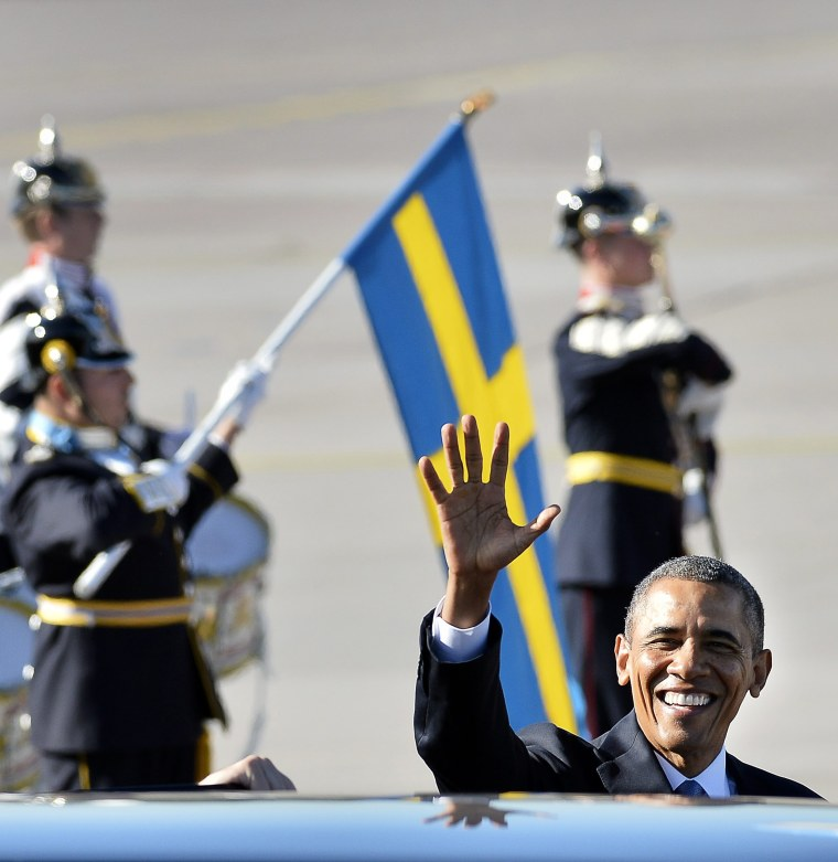 U.S. President Barack Obama waves upon arrival at Arlanda Airport, in Stockholm, Sweden, Wednesday, Sept. 4, 2013, with the Swedish flag and guard of honor in the background.