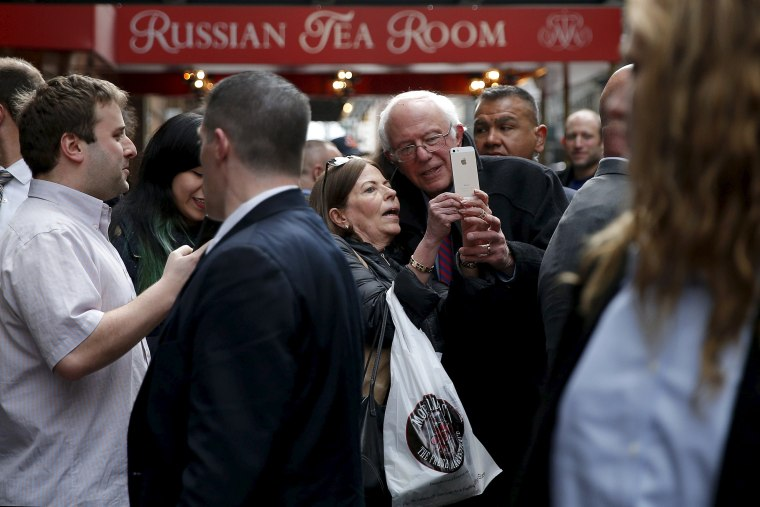 Image: U.S. Democratic presidential candidate and U.S. Senator Bernie Sanders poses for a selfie with a well-wisher while walking through midtown in New York City