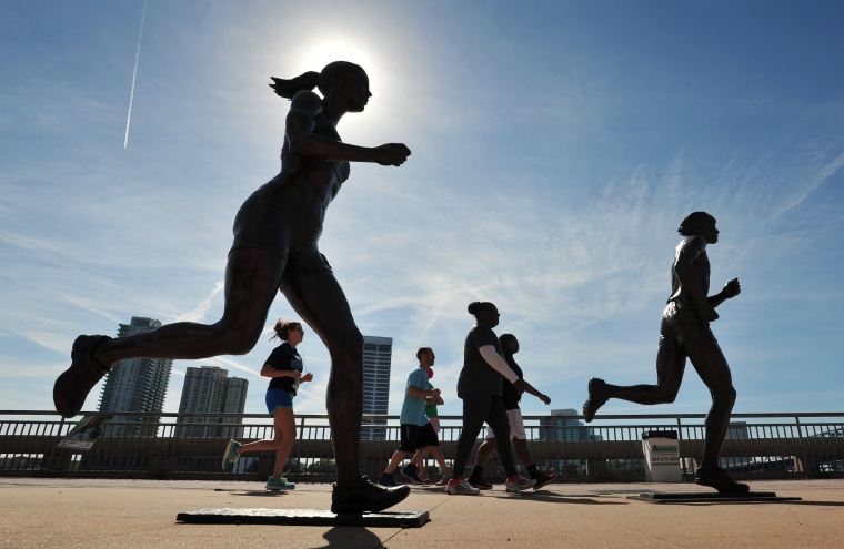Image: Runners make their way past the River Runner statues