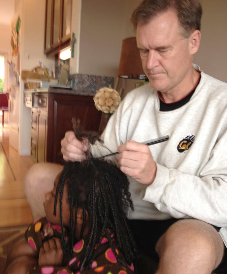 Father braids daughter's hair
