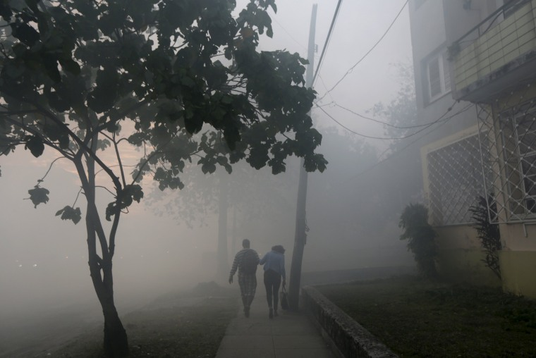 Image: People walk among clouds of insecticide after a fumigating truck moved past in Havana