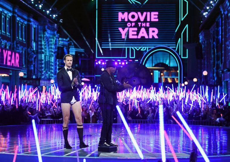 Image: Actors Alexander Skarsgard (L) and Samuel L. Jackson appear onstage as audience members wave 'Star Wars' lightsabers