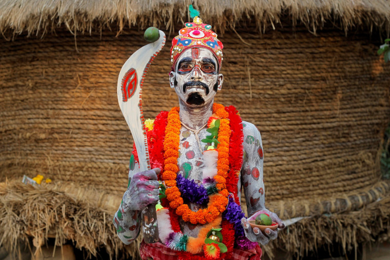 Image: A devotee with his body painted poses as he waits to perform during a ritual as part of the annual Shiva Gajan religious festival at Sona Palasi
