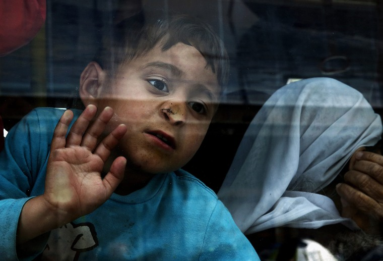 Image: A boy looks out of a bus window as refugees from Syria and Iraq board a bus