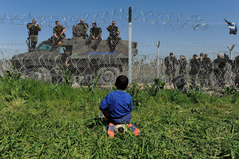 Image: A boy sits on his ball next to a border fence on the Greek side of the border, as Macedonian police stand guard on the Macedonian, near the Greek village of Idomeni