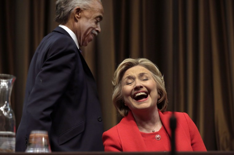 Image: Democratic presidential candidate Hillary Clinton laughs as the Rev. Al Sharpton walks to the podium