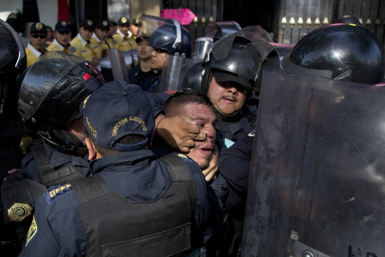 Image: Police detain a taxi driver protesting the one day per week driving restriction in Mexico City