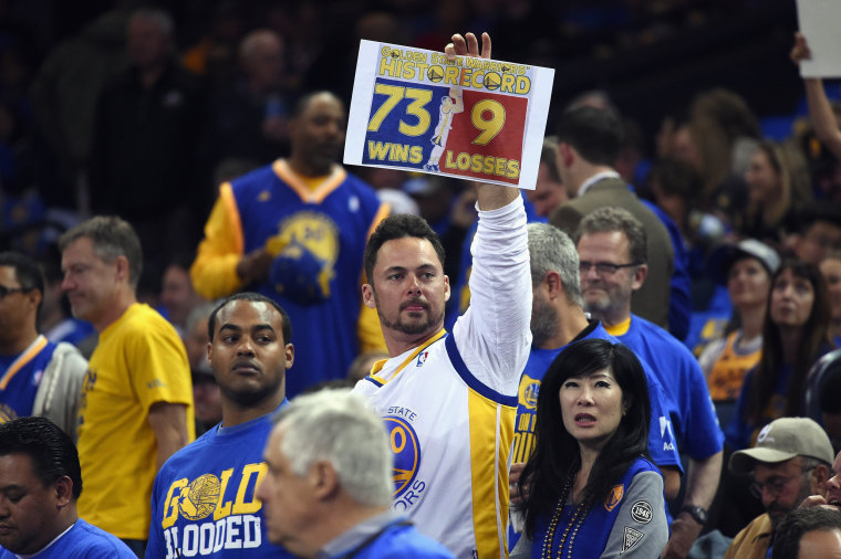 Image: A Golden State Warriors fan holds a sign prior to the game