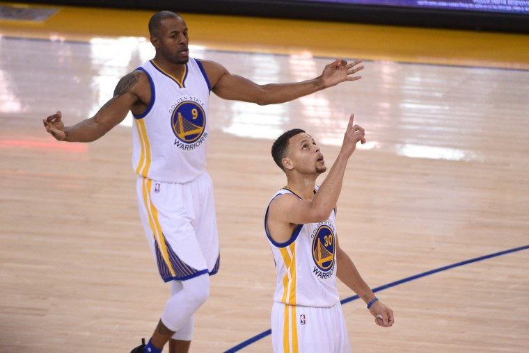 Image: Warriors guard Stephen Curry, no.30, and forward Andre Iguodala, no.9, celebrate Curry's three-point basket