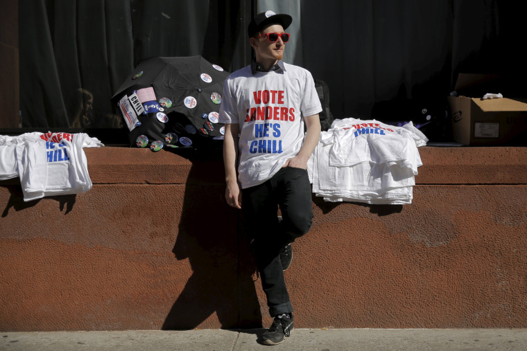 Image:  A supporter sells shirts before a campaign rally with U.S. Democratic presidential candidate Bernie Sanders in Washington Square Park in the Greenwich Village neighborhood of New York City