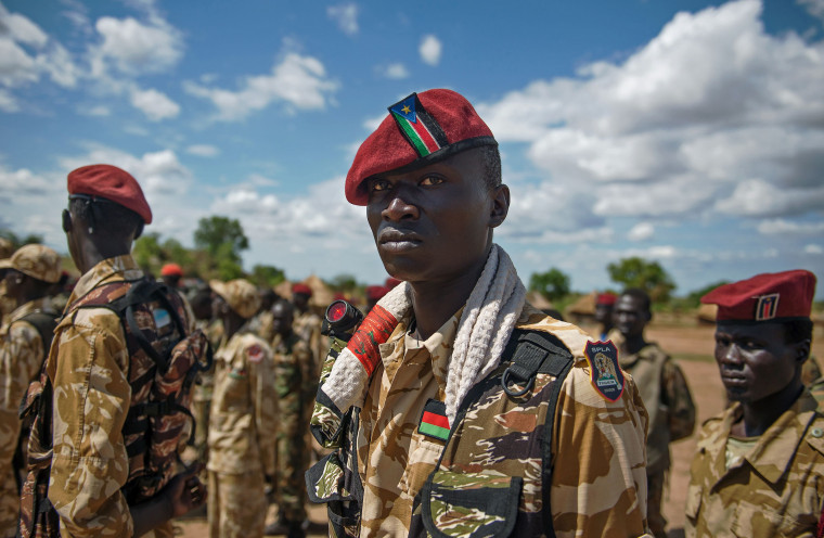 Image: The Sudan People's Liberation Army soldiers stand at attention at a containment site outside Juba