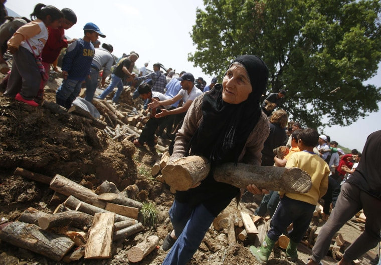 Image: A woman holds fire wood distributed near a makeshift migrant camp near Idomeni