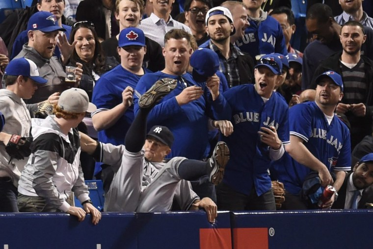 Image: New York Yankees' Brett Gardner falls into the stands after catching a foul ball