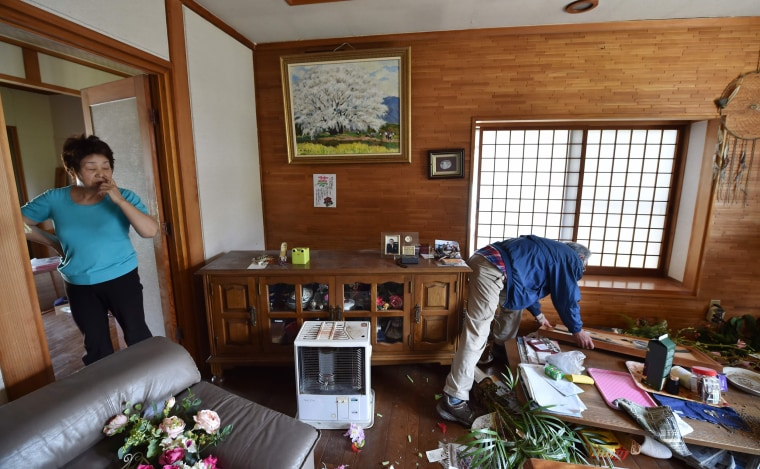 Image:  Nobuyuki Morita (R) and his wife assess the damage to their house