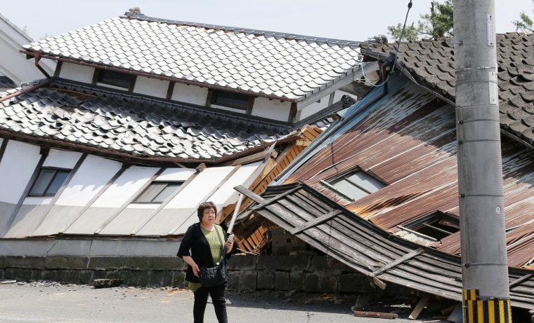 Image: A woman walks past destroyed houses