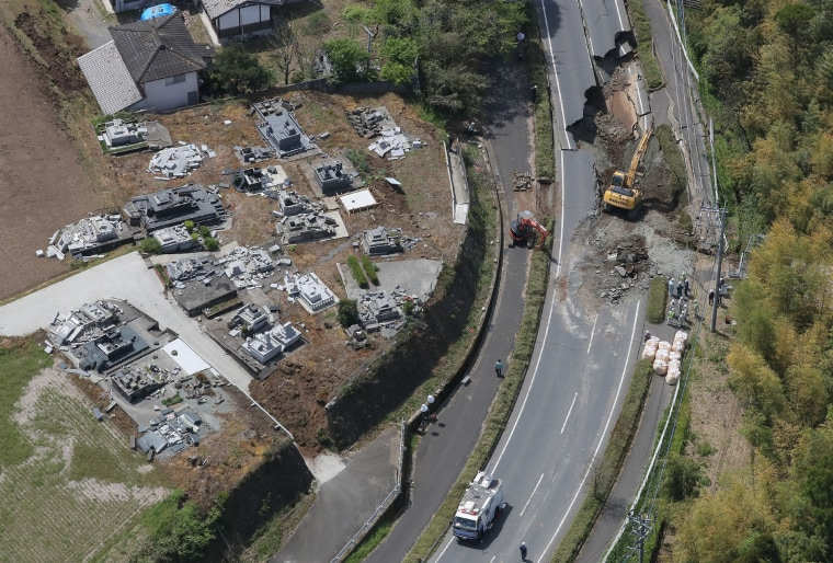 Image: An aerial view of construction workers restoring a damaged road located next to a grave yard