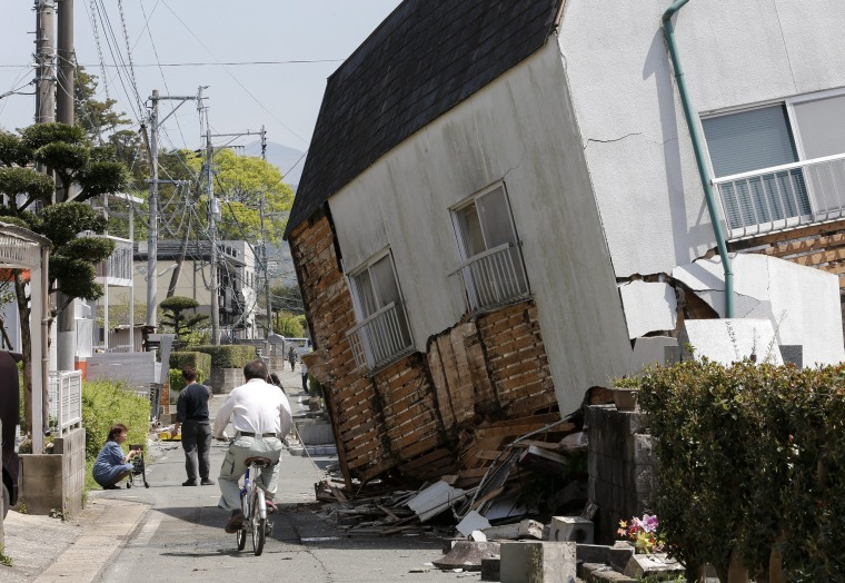 Image: A man cycles past a collapsed house