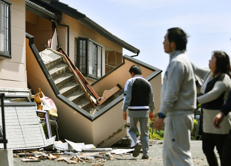 Image: Residents assess damage to a housing complex