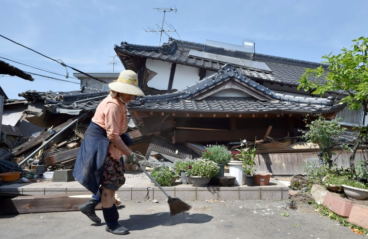 Image: A woman cleans up in front of her collapsed house in the town of Mashiki