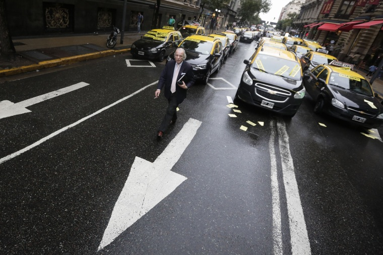 Image: A man walks through taxi drivers blocking an avenue to protest Uber in downtown Buenos Aires