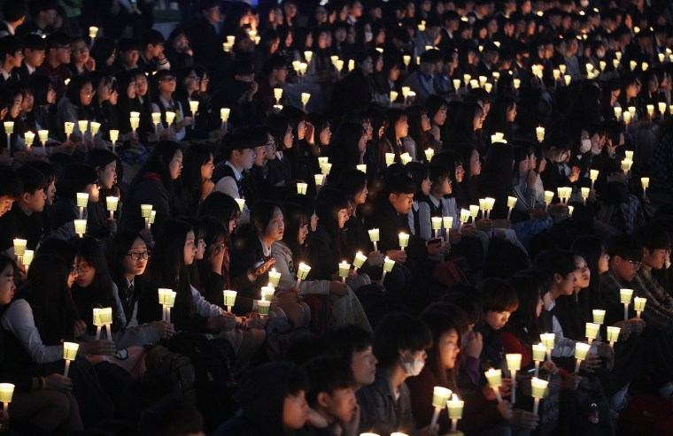 Image: High school students hold candles to pay their respects to the victims of the sunken ferry Sewol