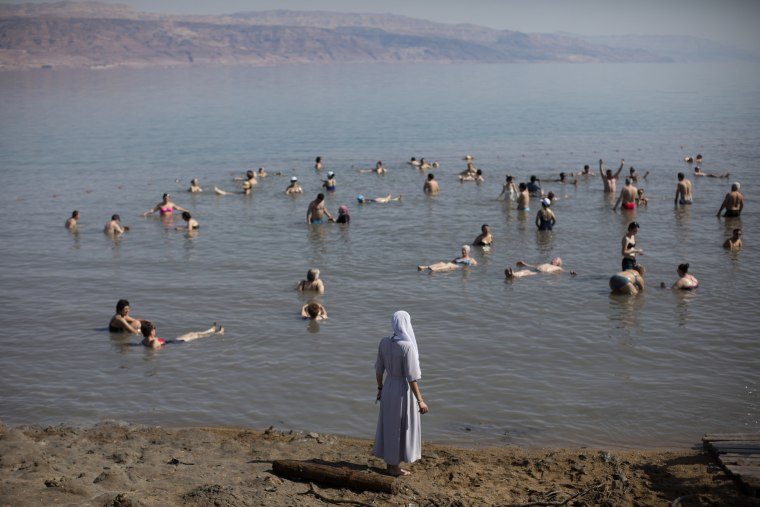 Image: Tourists float in the Dead Sea
