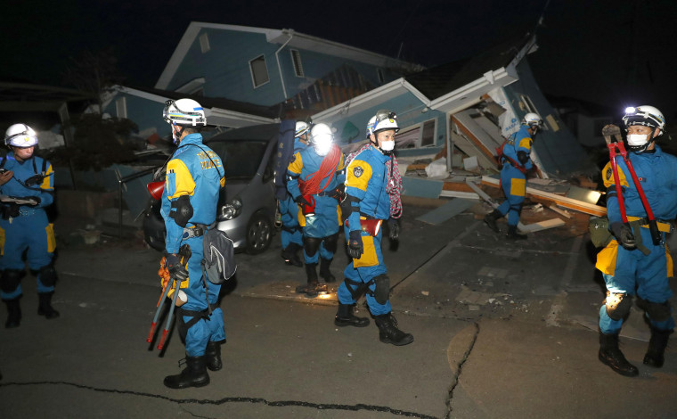 Image: Police officers investigate a house collapsed by an earthquake