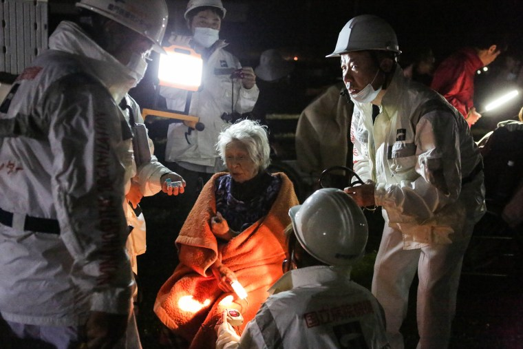 Image: Rescue workers take care of an elderly woman