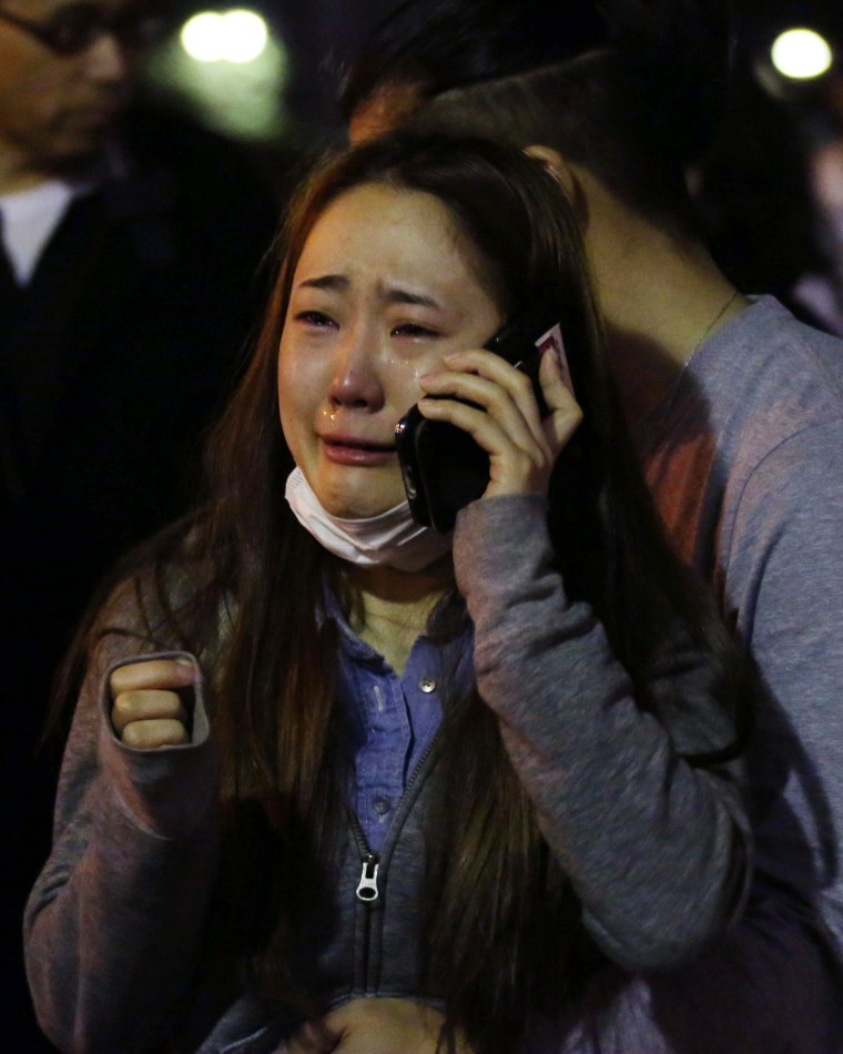 Image: An evacuee cries as she talks on a mobile phone at a park in Kumamoto