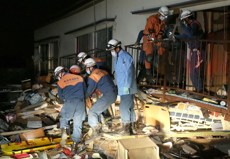 Image: Rescue workers save a person from a collapsed building in Kuammoto