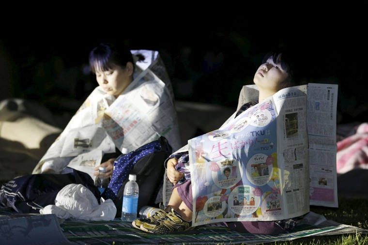 Image: Evacuees use newspapers to warm themselves at Prefectural University of Kumamoto after an earthquake in Kumamoto, southern Japan