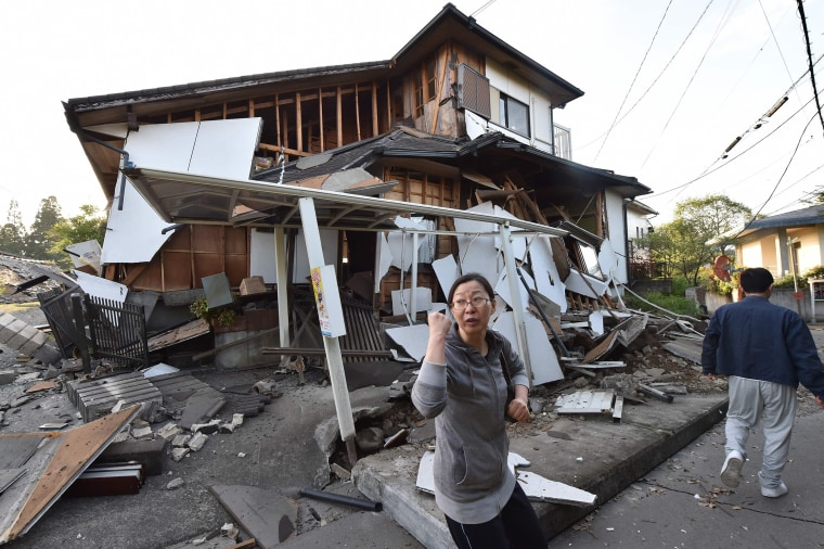 Image: A couple heads to their home past a collapsed house