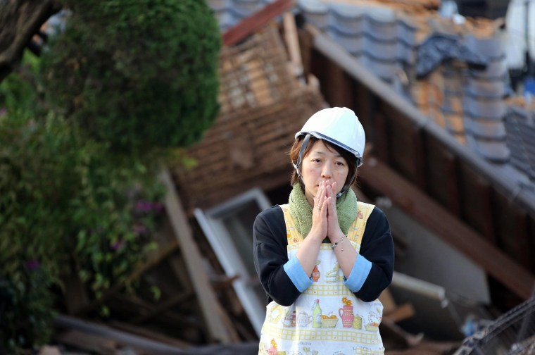 Image: A residents stands in front of a damaged house in Mashiki