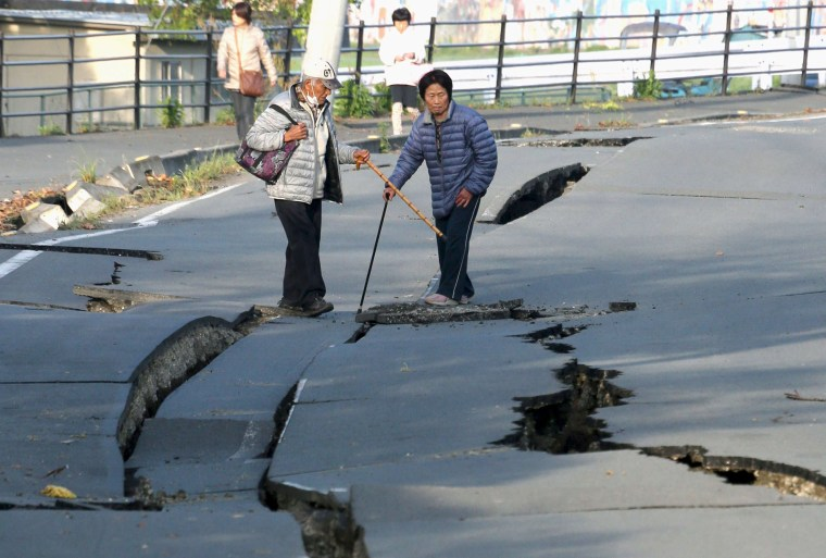 Image: Local residents look at cracks caused by an earthquake on a road in Mashiki town
