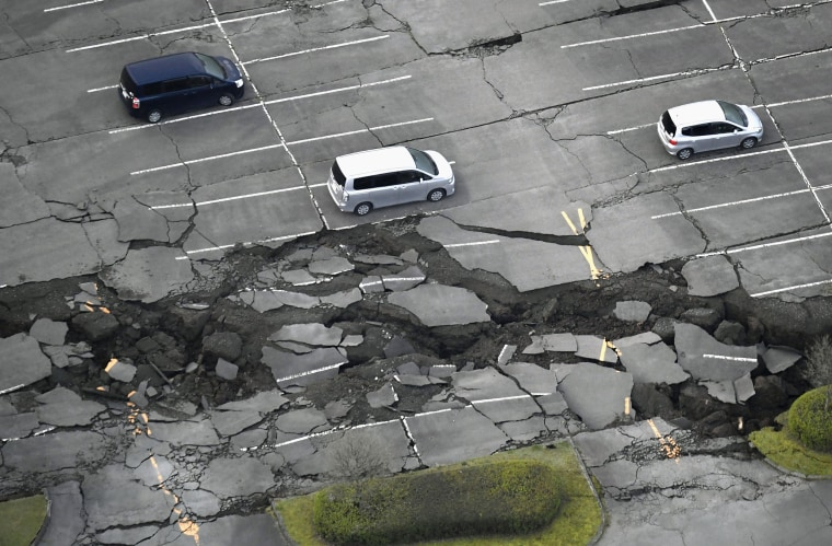 Image: Vehicles sit in a parking lot damaged by an earthquake