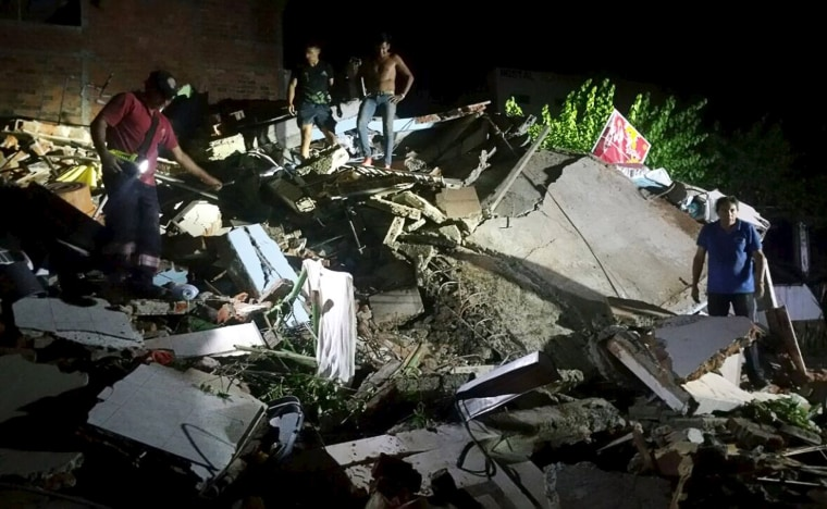 """Image: People stand next to the debris of a building after a 7.8 magnitude earthquake struck off the country's northwest Pacific coast causing \""""considerable damage\"""", in Manta"""