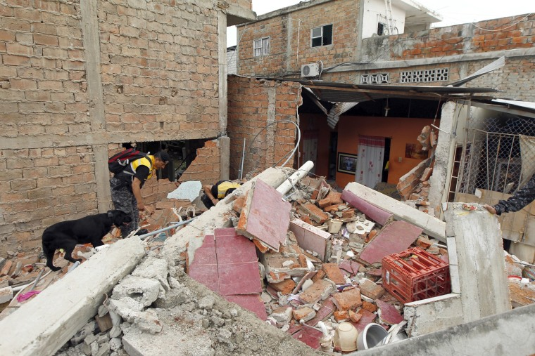 Image: Police officers search through debris after an earthquake struck off Ecuador's Pacific coast, at Tarqui neighborhood in Manta