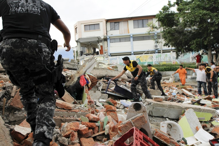 Image: Red Cross members, military and police officers work at a collapsed area after an earthquake struck off Ecuador's Pacific coast, at Tarqui neighborhood in Manta