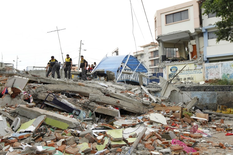 Image: Police officers stand on debris after an earthquake struck off Ecuador's Pacific coast, at Tarqui neighborhood in Manta