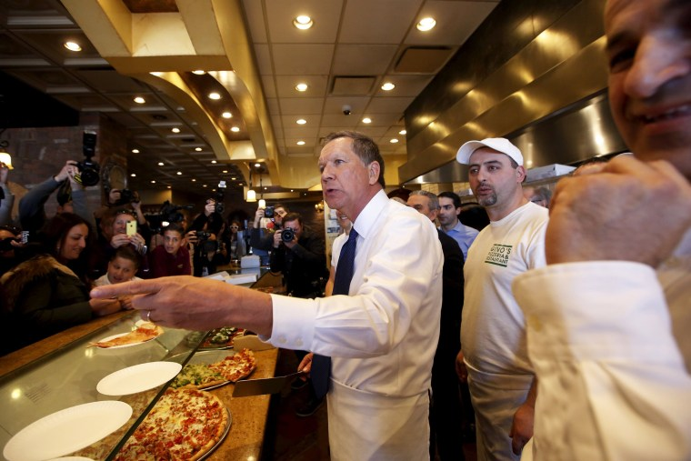 Image:  U.S. Republican presidential candidate John Kasich takes an order for a slice of pizza to a customer at Gino's Pizzeria and Restaurant in the Queens borough of New York