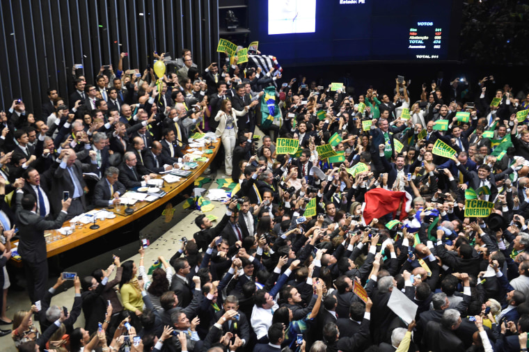 Image: Lawmakers celebrate the decision to proceed with impeachment proceedings against the president at the Congress in Brasilia